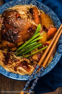 These spicy chicken noodles feature a super rich broth with juicy chicken. Learn to use the steam braising skill to cook a very flavorful chicken in much less time! | omnivorescookbook.com
